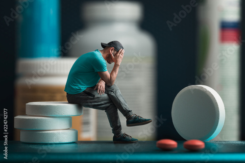 Obraz The man sitting on the pills. He's depressed. Flacons of medicines in the background - fototapety do salonu