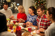 holidays and celebration concept - friends holding hands and praying while having christmas dinner at home