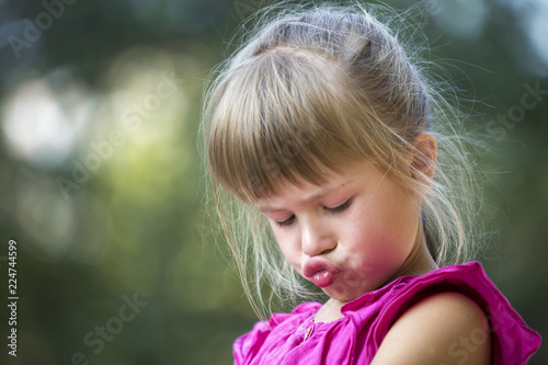 Fotografie, Obraz  Close-up portrait of pretty funny moody young blond preschool child girl in pink sleeveless dress feeling angry and unsatisfied on blurred summer green copy space background