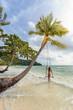 Young sexy girl in bikini on a swing on an exotic tropical sandy Bai Sao beach in the sea under a palm tree