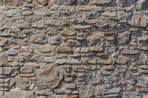 A beautiful horizontal texture of part of a old crushed natural stone different size wall in brown and gray hue