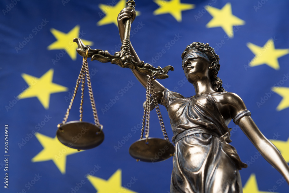 Fototapeta Statue of the blindfolded goddess of justice Themis or Justitia, against an European flag, as a legal concept