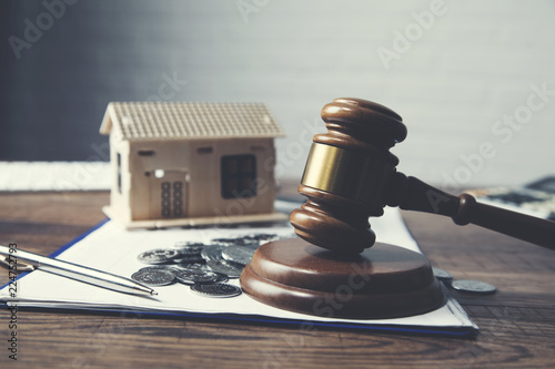 Photo Gavel with house model and coins on table