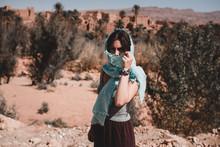 Young Woman In Kerchief Standing In Desert