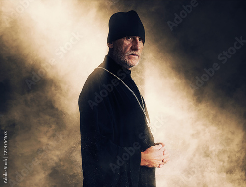 Fotografia Portrait of an elderly priest with gray hair in black clothes