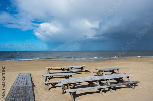 Staande foto Strand Wooden tables and benches of a summer cafe on a deserted beach in the bright sunny day of the beginning of autumn.