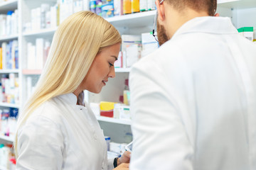 Colleagues pharmacists and chemists working at pharmacy drugstore