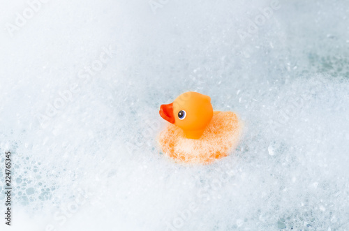 Photo Orange playful rubber duck in a bubble bath, light blue background with bubbles