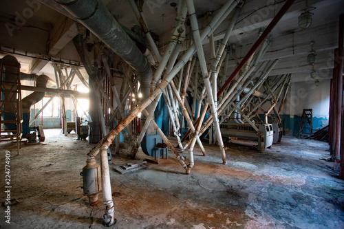 Foto op Canvas Oude verlaten gebouwen Abandoned flour milling factory. Old rusty roller mill equipment with pipeline