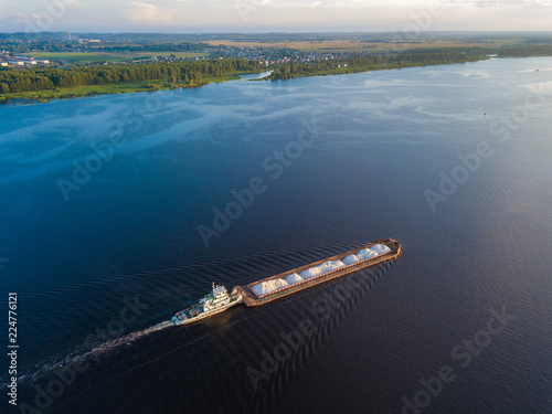 Aerial view carrier ship on river Volga. Cargo ship photo from drone.