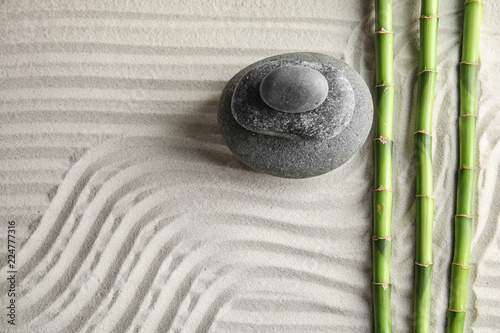 Tuinposter Stenen in het Zand Bamboo branches with spa stones on sand, top view. Space for text