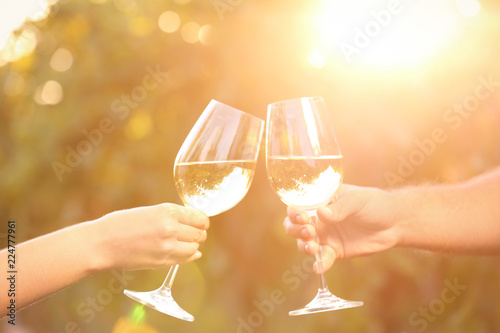 Couple with glasses of white wine outdoors, closeup