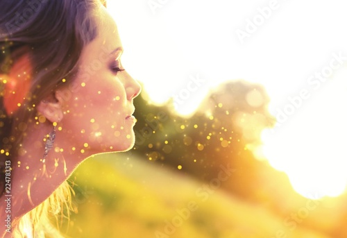 Fotografie, Obraz  Young woman on field under sunset light