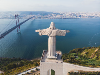 View of The Sanctuary of Christ the King, Cristo Rei, Almada, Lisbon, with 25 de Abril Bridge suspension Bridge, Tagus river, aerial drone view in summer sunny day