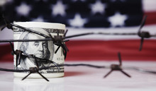 US Dollar Money Wrapped In Barbed Wire On United States National Flag Background As Symbol Of Economic Warfare, Sanctions And Embargo Busting