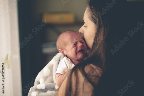 Photo Sweet crying newborn baby at mom on hand lifestyle