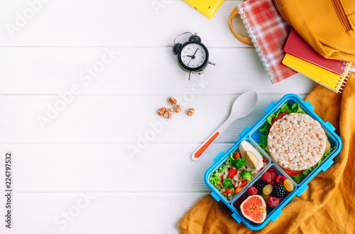 Lunch box on white wooden background near school accessories