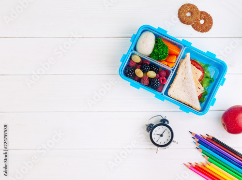 In de dag Assortiment Lunch box with sandwich, vegetables, berries on white wooden background with clock, school accessories