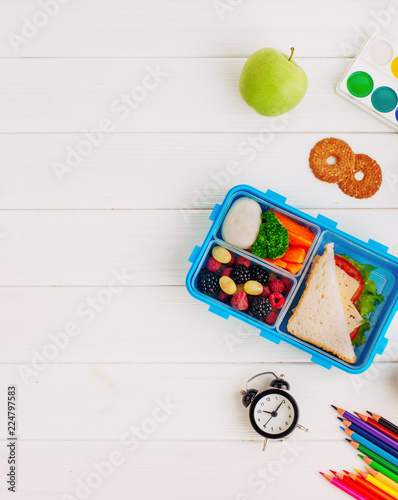 In de dag Assortiment Lunch box with sandwich, vegetables, berries on white wooden background with clock, watercolor and pencils