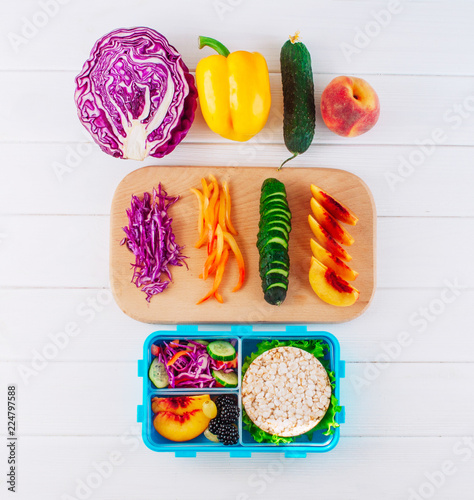 Open lunch box with sandwich, vegetables, egg, fresh berries on the white wooden background. Top view, flat lay.