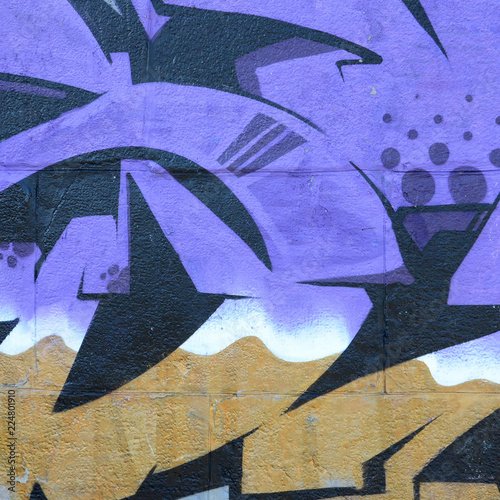 Fragment rysunków graffiti. Stara ściana ozdobiona plamami farby w stylu kultury ulicznej. Kolorowe tło tekstury w odcieniach fioletu