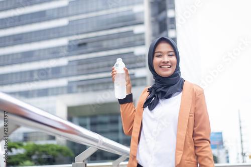 Beautiful young asian muslim drinking water. Fototapete