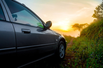 Fototapeta na wymiar Travel concept car against sunrise and trail on mountains. Close Up photo of off-road wheel