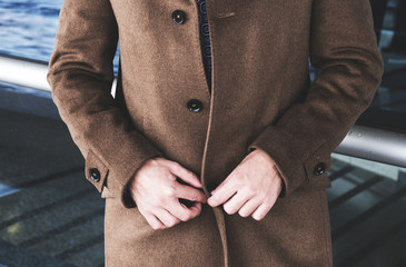 The man undoes a coat