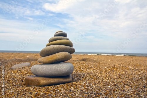 Tuinposter Stenen in het Zand Stones pyramid on sand symbolizing zen, harmony, balance. Sea in the background