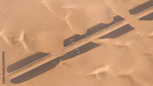 Canvas Prints Abu Dhabi Aerial view of a desert road being run over by sand dunes photographed from a drone at sunrise. Dubai, UAE.