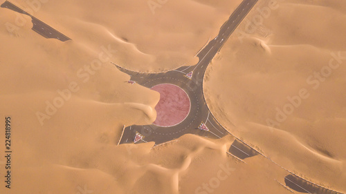 Fotoposter Abu Dhabi Aerial view of a desert road being run over by sand dunes photographed from a drone at sunrise. Dubai, UAE.