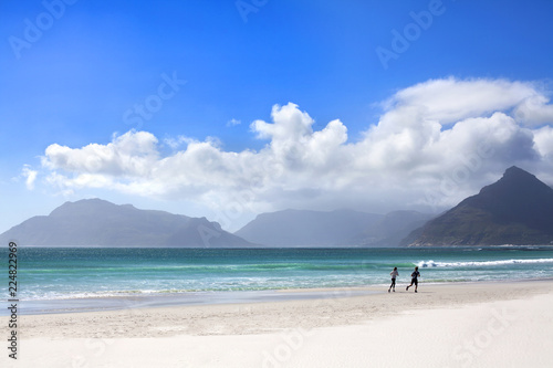 Girl and boy running on white sand beach, blue sea, waves, sky and mountains wit Wallpaper Mural