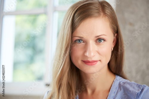 Face of very beautiful young smiling woman with blond hair looking at camera