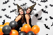 Two Charming Young Women In Witches Hats Hold Black And Orange Balloons On A White Background With Black Bats. Confetti Around