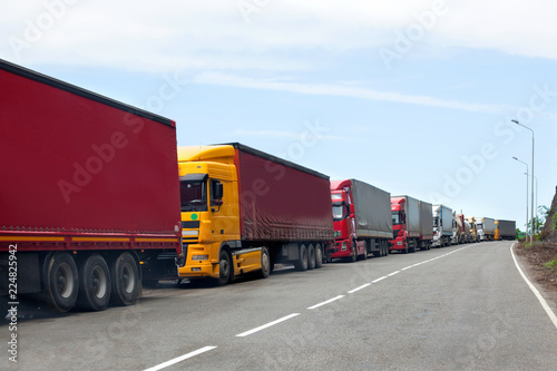 Fototapeta Queue of trucks passing the international border, red and different colors trucks in traffic jam on the road obraz