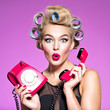 canvas print picture - young woman with wonder face holds retro phone