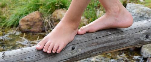 Cuadros en Lienzo Mädchen balanciert mit nackten Füßen über einen dünnen Baumstamm