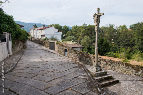 Stone Cross and street in Allariz, province of Ourense. Galicia. Spain.