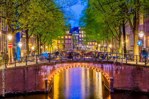 Amsterdam canal with typical dutch houses and bridge during twilight blue hour in Holland, Netherlands