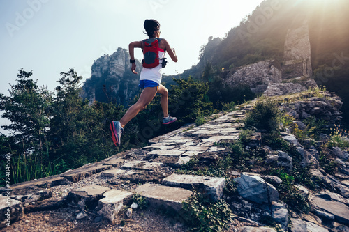 Fototapeta Sporty fitness woman runner running on mountain top obraz na płótnie