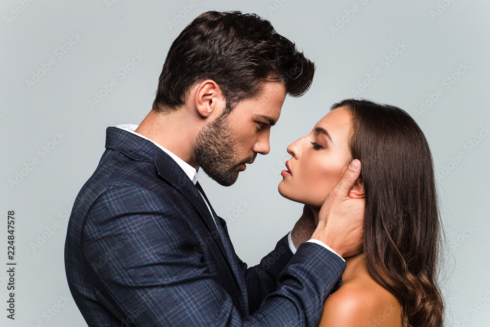 Fototapeta Give me a kiss. Portrait of young beautiful couple looking at their eyes while standing against white background