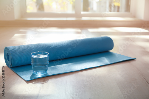 Obraz Yoga mat and glass of water on floor indoors - fototapety do salonu