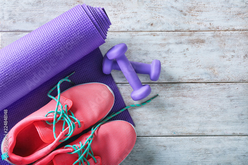 Fototapeta Yoga mat with sport shoes and dumbbells on light wooden background obraz