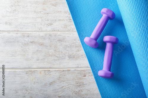 Fotografia  Yoga mat with dumbbells on light wooden background