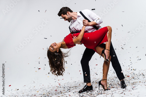 It is hot salsa! Full length of young beautiful couple dancing while standing against white background with confetti  - 224848724