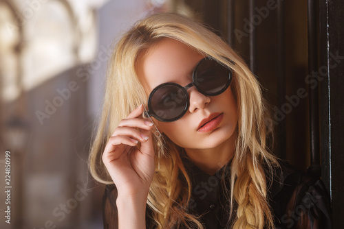 Outdoor close up portrait of young beautiful fashionable woman wearing black round sunglasses, blouse, posing in street of european city. Female fashion concept. Copy, empty space for text