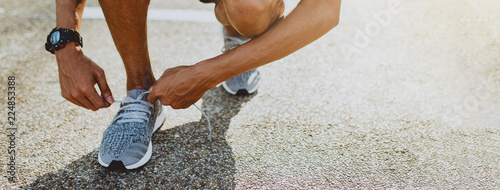 Man tying running shoes getting ready for run. Healthy lifestyle and sport. Banner with copy space.