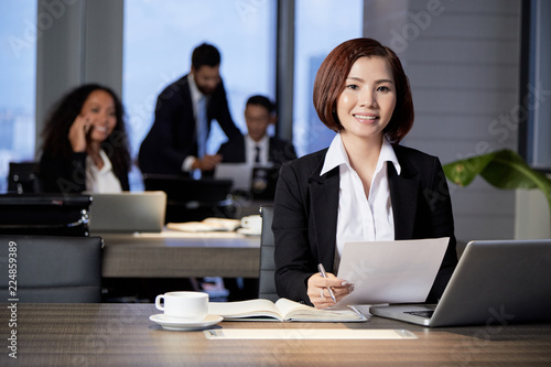 Smiling young ethnic woman with papers at table in modern office looking at camera with colleagues on background
