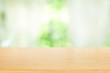 Empty of wooden table top on blur of abstract green from garden with sunlight and curtain window background , product display, for display or montage of product