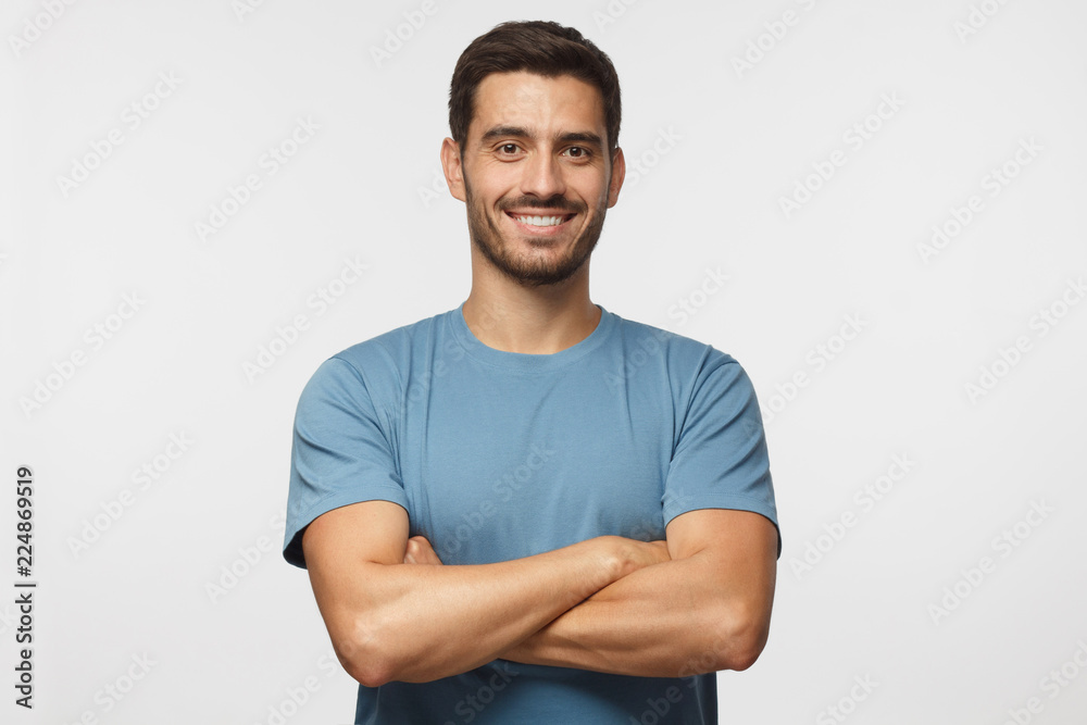 Fototapeta Indoor portrait of young european caucasian man isolated on gray background, standing in blue t-shirt with  crossed arms, smiling and  looking straight at camera